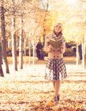 少妇有与书的步行在公园 免版税库存图片
