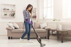 少妇有吸尘器的清洁房子 库存图片