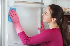 少妇有旧布的清洁冰箱在家 免版税图库摄影