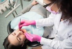 少妇有牙齿检查在牙齿诊所 牙医有牙齿工具的审查的患者` s牙 库存图片