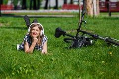 少妇松弛近的自行车在公园 免版税图库摄影