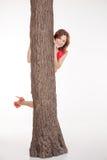 少妇查找从结构树的后面 免版税库存图片