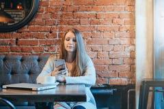 少妇正面图坐在咖啡馆和用途智能手机的桌上 在线教育 免版税库存照片
