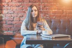 少妇正面图有长的头发的坐在咖啡馆和用途智能手机的桌上 图库摄影