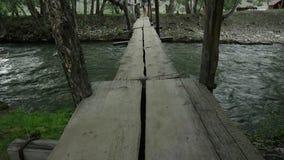 少妇沿在山河的一个狭窄的木桥走 野营和冒险概念 股票录像