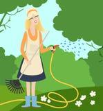 少妇浇灌的花在庭院里 免版税图库摄影