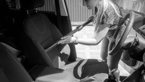 少妇清洁与吸尘器的汽车座位黑白照片  库存照片