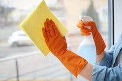 少妇清洁玻璃窗在家 库存照片