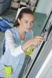 少妇清洁窗口 免版税图库摄影