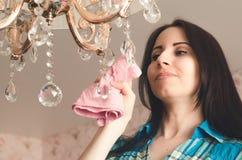 少妇清洗枝形吊灯与旧布 免版税图库摄影