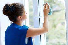 少妇清洁玻璃窗 Cleaning Company工作者 免版税库存照片