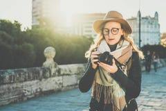 少妇游人,帽子的摄影师和镜片,在城市街道上站立并且使用照相机,看在屏幕上的图象 免版税库存照片