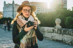 少妇游人,摄影师,帽子的行家女孩在城市街道上站立并且使用照相机,看在屏幕上的图象 库存照片