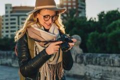 少妇游人,摄影师,帽子的行家女孩在城市街道上站立并且使用照相机,看在屏幕上的图象 库存图片