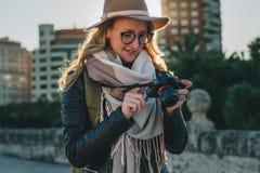 少妇游人,摄影师,帽子的行家女孩在城市街道上站立并且使用照相机,看在屏幕上的图象 免版税库存图片