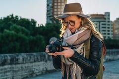 少妇游人,摄影师,帽子的行家女孩在城市街道上站立并且使用照相机,看在屏幕上的图象 免版税库存照片