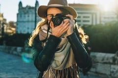 少妇游人,摄影师,行家女孩在帽子和镜片,在城市街道上的立场穿戴了并且拍照片 免版税库存图片