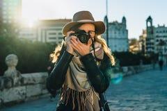 少妇游人,摄影师,行家女孩在帽子和镜片,在城市街道上的立场穿戴了并且拍照片 免版税库存照片