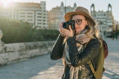 少妇游人,摄影师,行家女孩在帽子和镜片,在城市街道上的立场穿戴了并且拍照片 库存照片