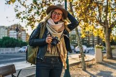 少妇游人,摄影师,行家女孩坐在城市街道上的长凳并且拍照片 假期,旅行,冒险 免版税库存图片