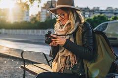 少妇游人,摄影师,行家女孩坐在城市街道上的长凳并且拍照片 假期,旅行,冒险 库存图片