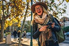 少妇游人,摄影师,行家女孩坐在城市街道上的长凳并且拍照片 假期,旅行,冒险 库存照片