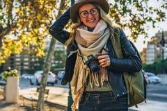 少妇游人,摄影师,行家女孩坐在城市街道上的长凳并且拍照片 假期,旅行,冒险 免版税库存照片
