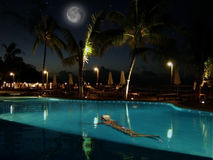 少妇游泳。美丽的夜水池 免版税库存照片