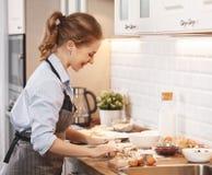 少妇烘烤曲奇饼在家在厨房里 免版税图库摄影