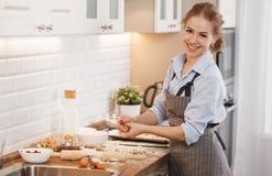 少妇烘烤曲奇饼在家在厨房里 库存图片