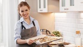 少妇烘烤曲奇饼在家在厨房里 免版税库存图片