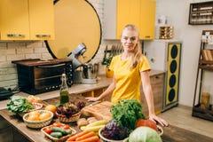 少妇烹调在厨房的,健康食物 免版税库存照片