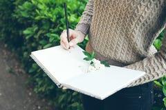 少妇特写镜头递写下未来她的希望和梦想入她的日志,做计划 库存图片