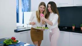 少妇用可口沙拉在摆在为在智能手机的照片的手上在烹调 影视素材