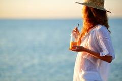 少妇用在一次性杯子的橙汁反对海 免版税库存照片