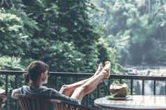 少妇用在瀑布背景的新鲜的有机椰子在巴厘岛密林  库存照片