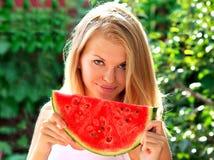 少妇用大切片西瓜莓果新鲜在手美丽的微笑的面孔 库存照片