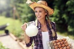 少妇用新鲜的有机鸡蛋和牛奶 免版税图库摄影