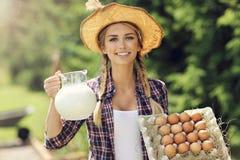 少妇用新鲜的有机鸡蛋和牛奶 图库摄影