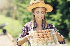 少妇用新鲜的有机鸡蛋 免版税库存图片