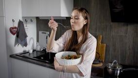 少妇由匙子在手上吃菜沙拉,拿着大白色色拉盘,站立在一个厨房里在晚上 影视素材