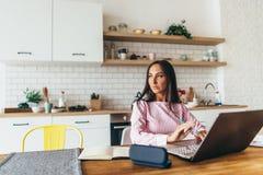 少妇画象在桌上在运作的厨房里坐膝上型计算机 库存图片