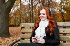 少妇画象在秋天公园,听到在耳机的音乐 免版税图库摄影
