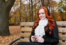 少妇画象在秋天公园,听到在耳机的音乐 库存图片