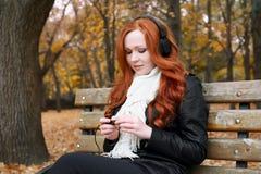 少妇画象在秋天公园,听到在耳机的音乐 免版税库存图片
