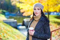 少妇画象有咖啡的在秋天公园 库存照片