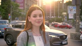 少妇画象有看在照相机和身分的姜头发的在城市街道上在日落期间,微笑,交易 股票录像