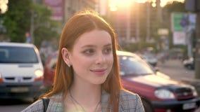 少妇画象有站立在街道和看在照相机的姜头发的在晚上期间,微笑,交通  影视素材