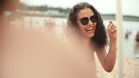 少妇画象比基尼泳装的与朋友坐海滩和微笑 免版税库存照片