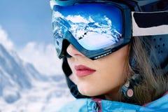 少妇画象滑雪胜地的在山和蓝天背景  山脉在滑雪帽反射了 免版税库存照片